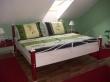 Kovaná postel Alcatraz v netradičním provedení v bílé barvě s červeným patinovaným dřevem.